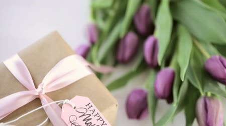 Small gift and purple tulips for Mothers Day. Stock mozgókép