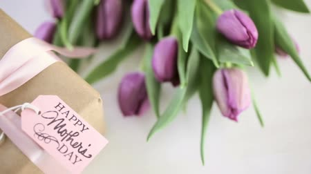 Small gift and purple tulips for Mothers Day. Stock Footage