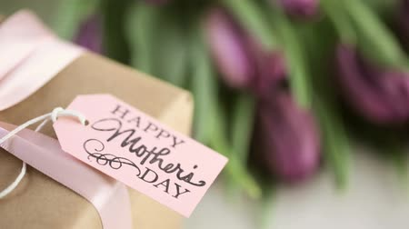 buket : Small gift and purple tulips for Mothers Day. Stok Video