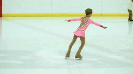 skate : Little girl figure skating at the indoor ice arena.