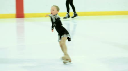 patenci : Little girl figure skating at the indoor ice arena.