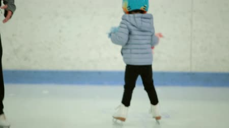 skate : Toddler girl learning how to ice skate on in door ice arena.
