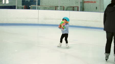 Toddler girl learning how to ice skate on in door ice arena.
