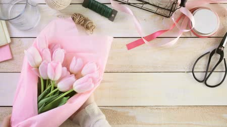 perene : Step by step. Florist wrapping pink tulips in bouquet.