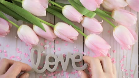 buket : Light pink tulips on a wood background.