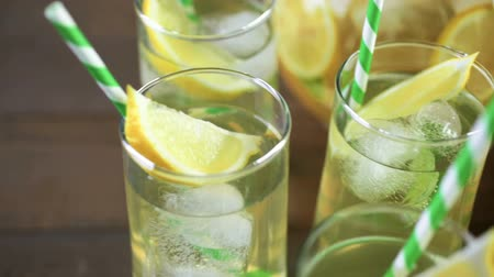 Green tea with citrus in glasses with ice and paper straw. Stock mozgókép