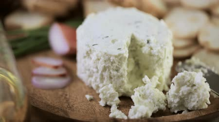 perene : Soft flavored creamy cheese with garlic and fine herbs on a wood board with crackers.
