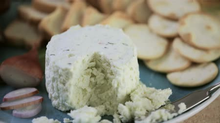 pişmiş : Soft flavored creamy cheese with garlic and fine herbs on a wood board with crackers.