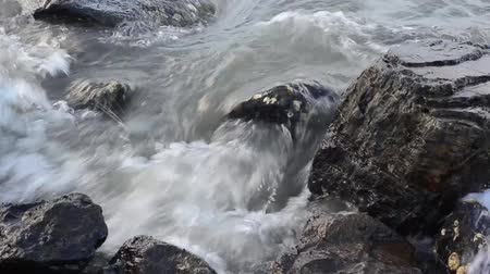 primordial : Waves crashing onto the rocks.This clip is an overhead view looking down at the rocky