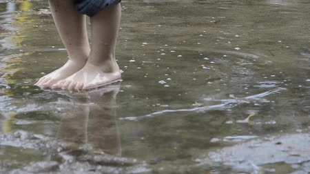 dirty : Feet of a kid enjoying to walk barefooted through puddles Stock Footage