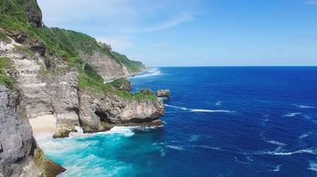 travel tropical : Aerial video of cliffed coast line and ocean. Bukit Peninsula Bali, Indonesia.