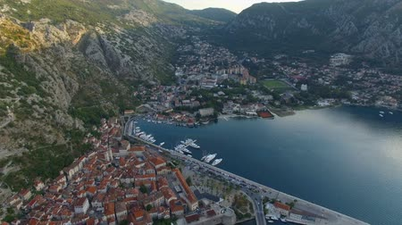 port n : Flying high above Kotor Montenegro old town, marina bay with pier and yachts towards mountain peaks.