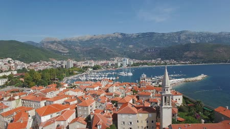 port n : Descend and landing on the red tile roofs in the old town of Budva with yachts and mountains on background