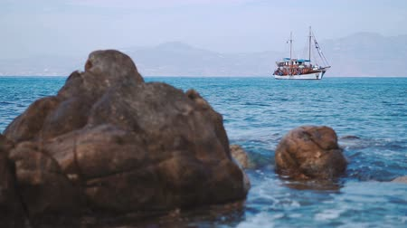 port n : Lonely schooner is anchored in the quiet harbor of the Mediterranean Sea near the coast of the island of Mykonos with defocused stones on foreground.