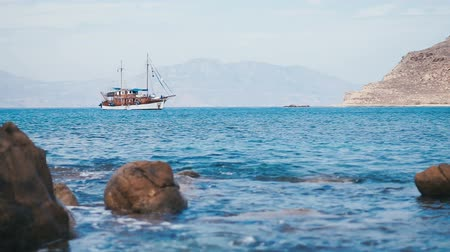 sail rock : Lonely vintage touristic schooner is anchored in the quiet harbor of the Mediterranean Sea near the coast of the island of Mykonos with defocused stones on foreground.