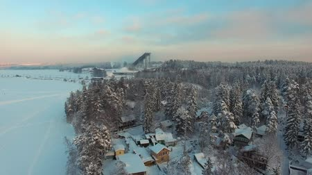 kayran : Rural winter landscape at sunset. Flying above frozen lake shore covered in snow, coniferous forest with pines and firs, small village with country houses and cottages. Aerial footage.