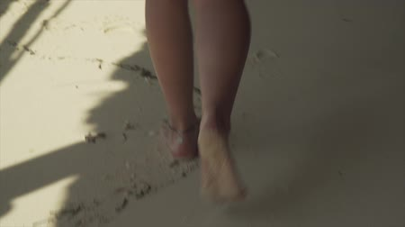 perna : Young caucasian girl walking on white sand beach and water along ocean. Close-up of legs and feet leaving footprints on sand at bright sunny day with hard shadows.