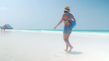 sunhat : Barefoot brunette girl in straw hat, shorts, bathing suit with bag walks on white beach of turquoise ocean on bright day. Yachts and boats, tourists, wood structure with thatched roof bridge. Zanzibar Stock Footage