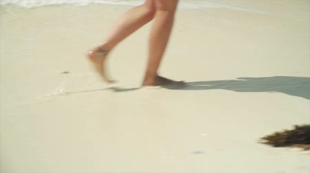 pegada : Young caucasian girl walking on white sand beach and water along ocean. Close-up of legs and feet leaving footprints on sand at bright sunny day with hard shadows.