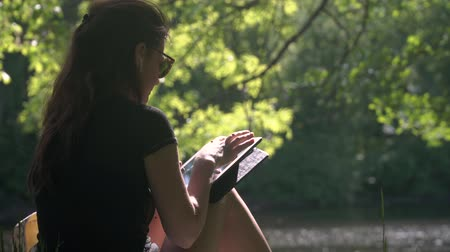 portátil : Young woman with wireless headphones uses digital tablet for learning and work. Student girl with sunglasses sitting on grass by the river in city park surrounded by trees and foliage at sunny day. Vídeos