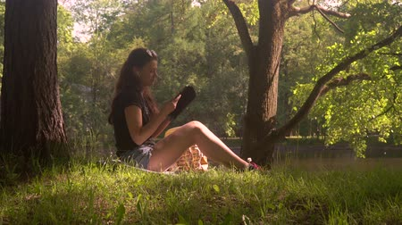portátil : Young woman with wireless headphones uses smartphone and digital tablet for learning and work. Student girl with sunglasses sitting on grass in city park surrounded by trees and foliage at sunny day.