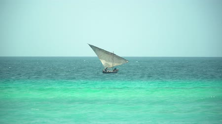 waters : Man working on traditional african wooden dhow boat that swinging on the waves of bright turquoise ocean on sunny day. Zanzibar, Tanzania, Africa.