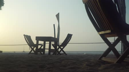 kafeterya : Empty outdoor street cafe restaurant on the beach at sunset. Wooden table and chairs stand on the sand on the beach near the ocean. Stok Video
