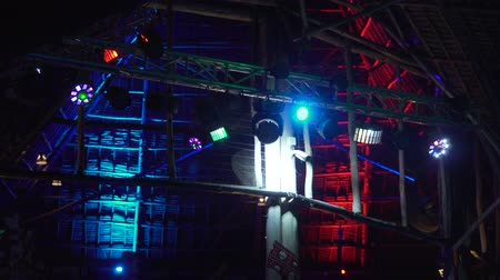 searchlight : bright colored spotlights are spinning and shining in different directions at a tropical party. multicolored light attached to the beams of a wooden building. Stock Footage