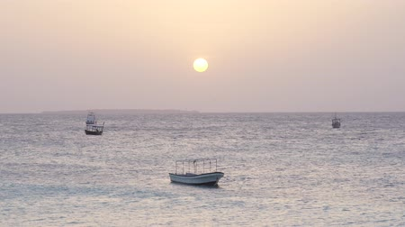 lancha : Small boats swing on silver ocean waves during the evening calm at sunset. Nungwi beach, Zanzibar, Tanzania, Africa.