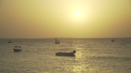 дрейф : Small boats swing on silver ocean waves during the evening calm at sunset. Nungwi beach, Zanzibar, Tanzania, Africa.