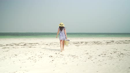 わら : Young caucasian woman walking barefoot on sandy beach towards turquoise ocean coastline. Adult european girl in straw hat and sundress with basket in hand walks on deserted paradise beach at sunny day