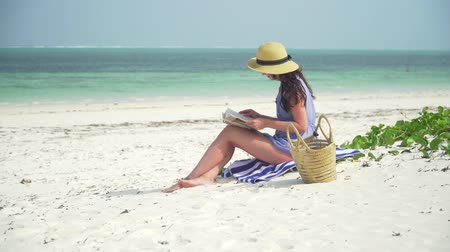 sunhat : Young european woman is reading a book on the emtpy paradise beach by ocean. Adult caucasian girl in straw hat and sundress sits on white sand near ocean and reads a book on clear hot bright sunny day