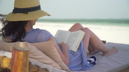 sunhat : Young woman is reading book on white sand beach by ocean. Adult caucasian girl in straw hat and sundress is lying on lounger sunbed in shadow on white sandy beach and reading book at bright sunny day. Stock Footage