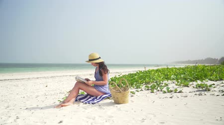 ler : Young european woman is reading a book on the emtpy paradise beach by ocean. Adult caucasian girl in straw hat and sundress sits on white sand near ocean and reads a book on clear hot bright sunny day