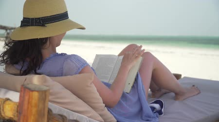 Young woman is reading book on white sand beach by ocean. Adult caucasian girl in straw hat and sundress is lying on lounger sunbed in shadow on white sandy beach and reading book at bright sunny day. Wideo