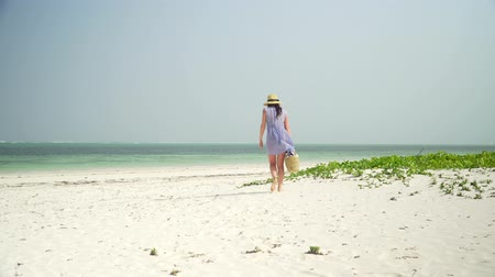 Young european woman is reading a book on empty paradise beach near ocean. Adult caucasian girl in straw hat and sundress sits on white sand, pulls book out of basket and reads it on bright sunny day.