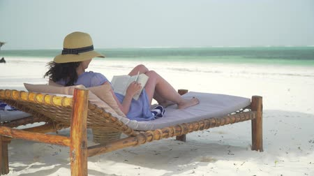 livros : Young woman is reading book on white sand beach by ocean. Adult caucasian girl in straw hat and sundress is lying on lounger sunbed in shadow on white sandy beach and reading book at bright sunny day. Stock Footage