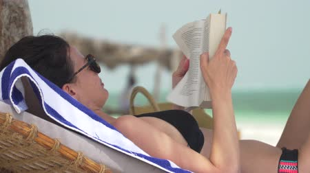 Young caucasian brunette woman is reading book on white sand beach near ocean. Adult girl in swimsuit and sunglasses lying in shadow on lounger sunbed on beach and reading a book at bright summer day. Wideo
