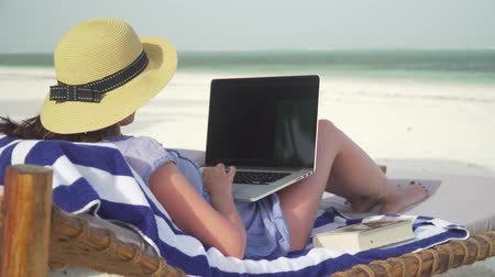 A young woman uses a laptop on a white beach near the ocean. Adult caucasian girl in straw hat and sundress is lying on lounger sunbed on white sand coast line and typing on laptop at bright suny day
