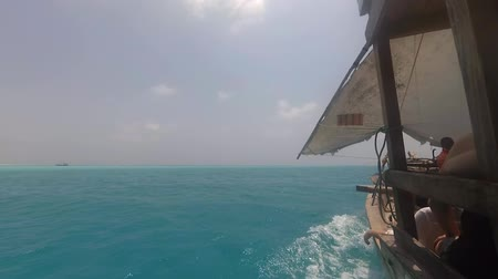 Traditional wooden Dhow boat with tourists sailing fast through ocean waves on bright sunny day. Sea horizon with tropical island and blue sky in background. View from left side of boat. Timelapse. Wideo