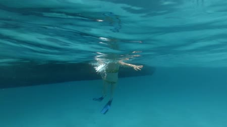 Young woman in a bathing suit and flippers coming down from the wooden boat into the blue water. Underwater footage.