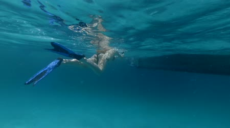 Young woman in a swimsuit and flippers slowly swims to a wooden boat in the open waters of the ocean. Underwater footage.