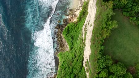 Flight along high cliffs of rocky shore of Indian Ocean. Top down view of ocean frothy waves break on sharp rocks with green vegetation on top. Aerial footage of Uluwatu coastline, Bali, Indonesia.