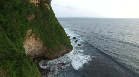 Flight along the high cliffs of the rocky shore of the Indian Ocean. The frothy waves of the ocean break on sharp rocks. The coastline of Uluwatu village on the island of Bali, Indonesia.