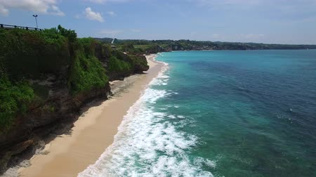 Long sandy beach on tropical island surrounded by cliffs with green vegetation on top and azure Indian Ocean with frothy waves on bright sunny day. Aerial footage of Dreamland beach, Bali, Indonesia. Wideo
