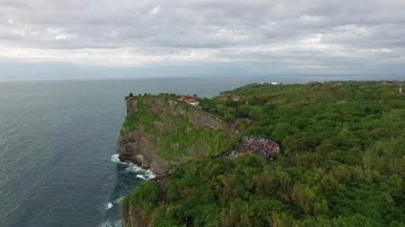 hava durumu : Flight above high cliffs of the rocky shore of Indian Ocean with green vegetation on top. The coastline of Uluwatu village on the island of Bali, Indonesia aerial footage at cloudy day.