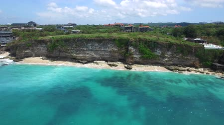 Sandy beach on tropical island surrounded by cliffs with green vegetation on top and azure Indian Ocean with frothy waves on bright sunny day. Aerial footage of Dreamland beach, Bali, Indonesia.