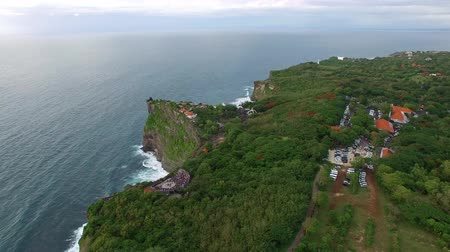 Flight above high cliffs of the rocky shore of Indian Ocean with green vegetation on top. The coastline of Uluwatu village on the island of Bali, Indonesia aerial footage at cloudy day.
