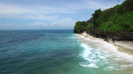 Flying low above long sandy beach surrounded by cliffs and azure Indian Ocean with frothy waves on bright sunny day. Tropical Aerial footage of Dreamland beach, Bali, Indonesia.