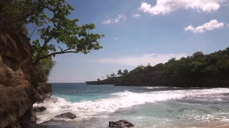 costa azzurra : Beautiful lagoon surrounded by rocks. Relaxing Landscape with overhanging cliff covered with vegetation and bushes washing by frothy waves of azure Indian Ocean. 50 frames per second full hd footage.